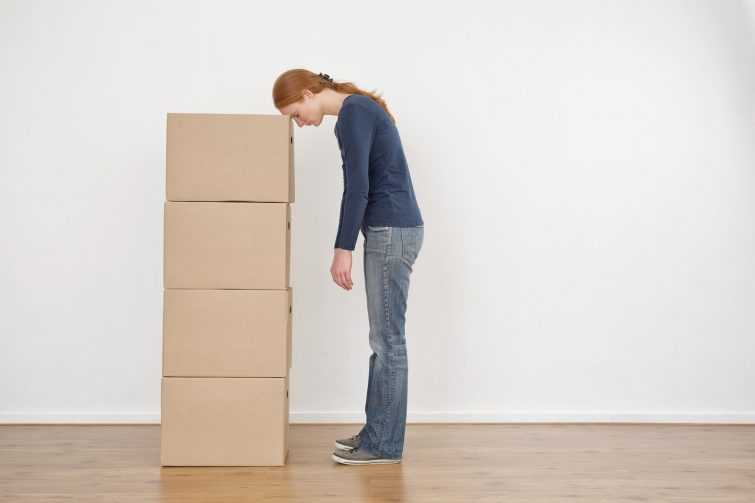 A tired or exhausted young woman resting her head on a stack of carton moving boxes in an empty room.
