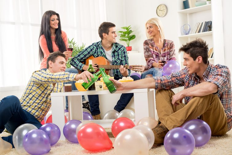 Small group of young people at the home party enjoy the sounds of the acoustic guitar drinking wine and beer.